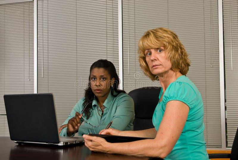 Twee bedrijfsvrouw die aan een laptop computer werken royalty-vrije stock afbeeldingen