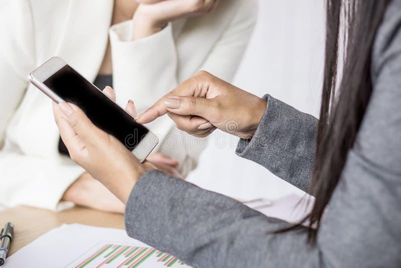 Twee bedrijfsvrouw die mobiele telefoon bekijken die over hun project spreken stock fotografie