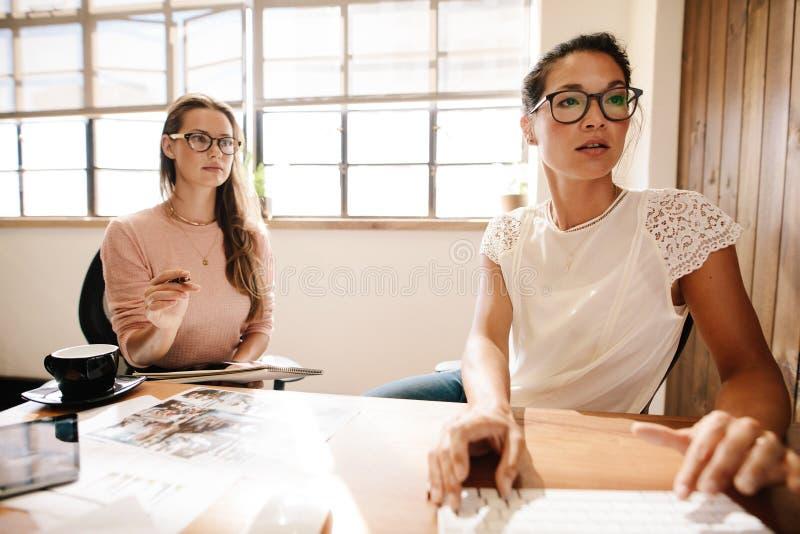 Twee bedrijfsvrouwen die bij bureau samenwerken stock afbeelding