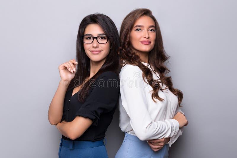 Twee bedrijfsvrouwen die met hun ruggen zich verenigen royalty-vrije stock afbeeldingen