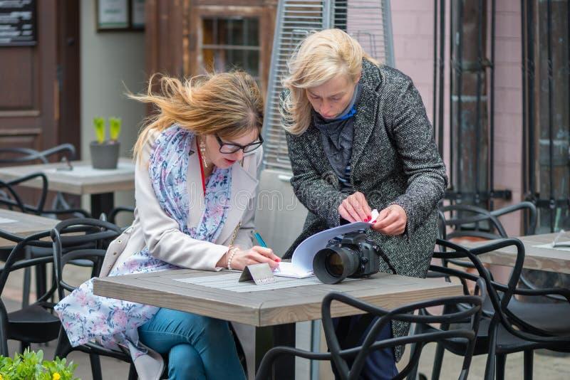 Twee bedrijfsvrouwen in een openluchtkoffie sloten de overeenkomst en het teken t stock afbeelding