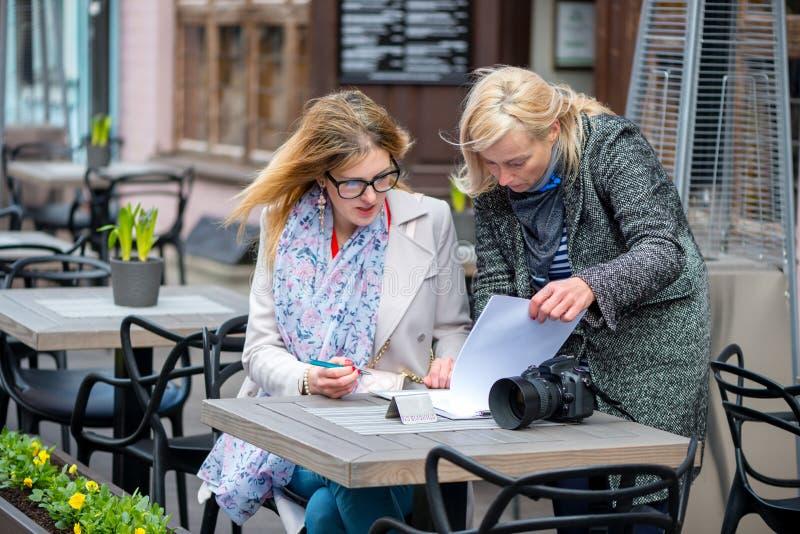 Twee bedrijfsvrouwen in een openluchtkoffie sloten de overeenkomst en het teken t stock foto