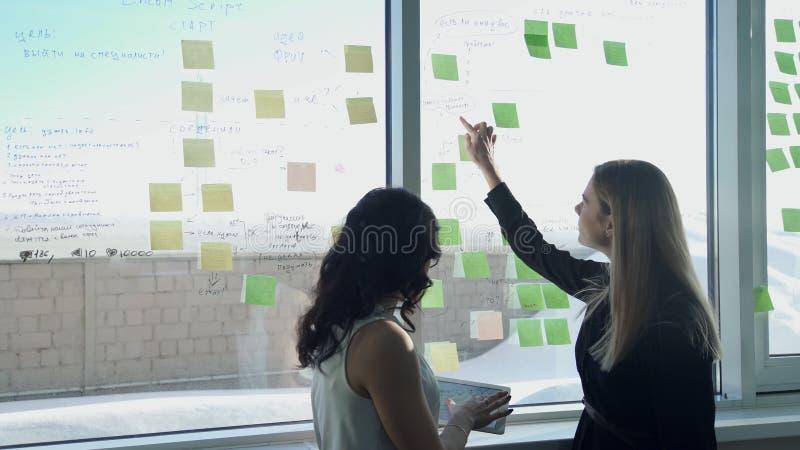 Twee bedrijfsvrouwen op achtergrond van venster in zaal bespreken onderwerpen