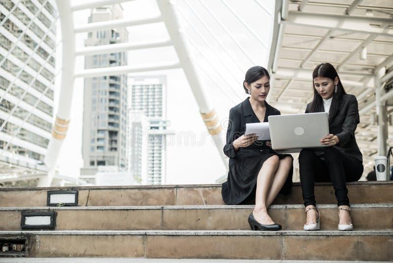 Twee bedrijfsvrouwen zitten op de trap en spreken over zaken met laptop en exemplaarruimte voor tekst stock foto