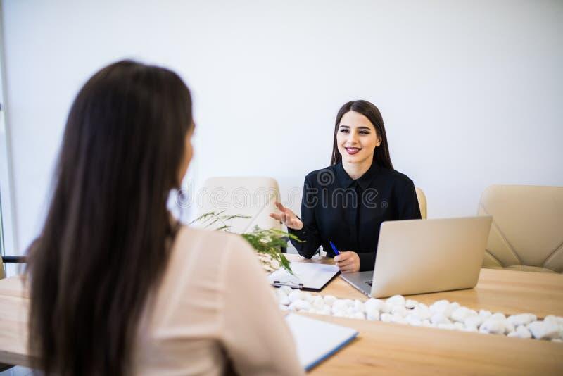 Twee bedrijfsvrouwenzitting bij bureau: klant en adviseur die samen in modern bureau spreken royalty-vrije stock afbeelding