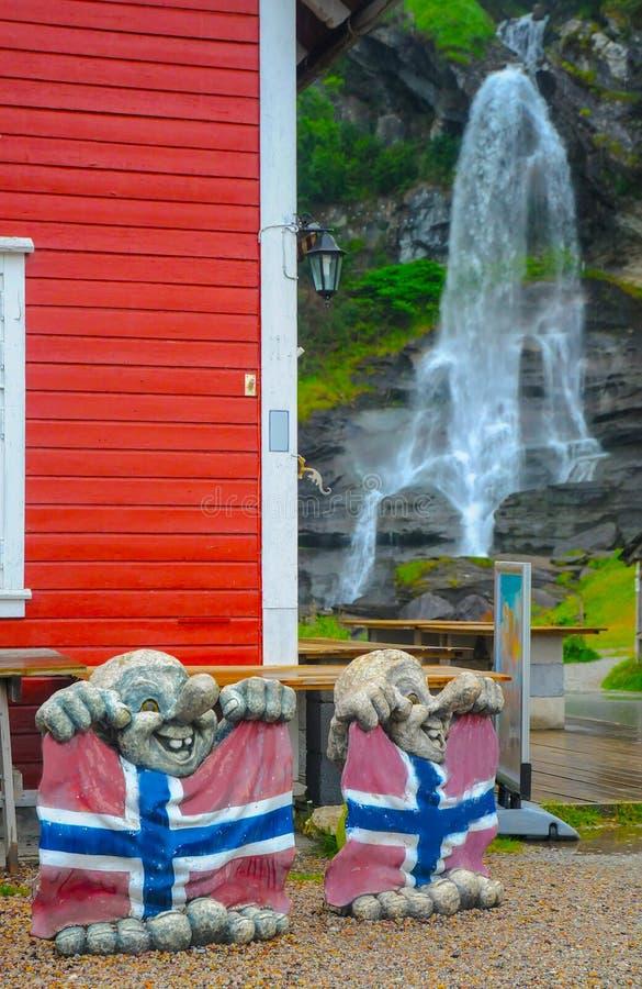 Twee beeldhouwwerken van sleeplijnen met Noorse vlaggen en Steinsdalsfossen-waterval op de achtergrond, Noorwegen stock afbeelding
