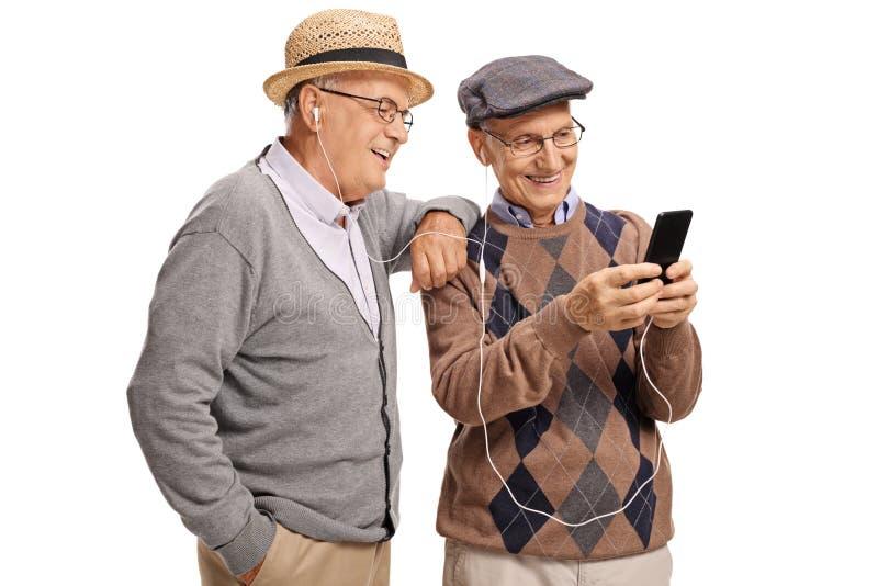 Twee bejaarden die aan muziek op een telefoon luisteren stock foto