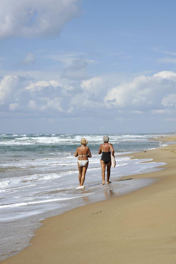 Twee bejaarden die en op het strand lopen spreken stock foto