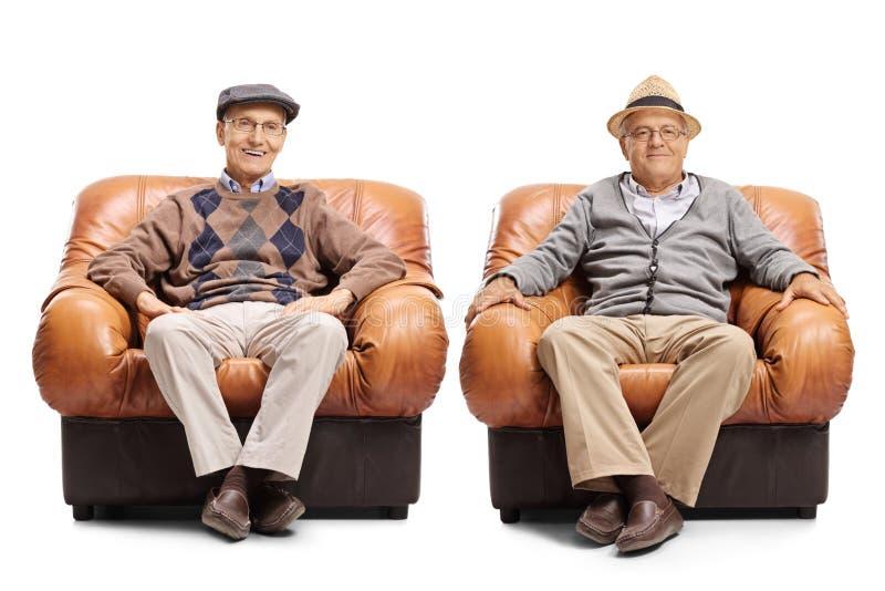Twee bejaarden die in leerleunstoelen zitten royalty-vrije stock afbeeldingen