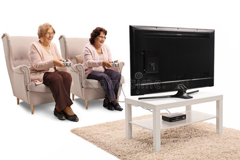 Twee bejaarden die in leunstoelen en het spelen videospelletjes i zitten royalty-vrije stock foto