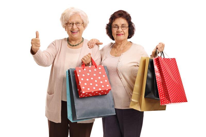 Twee bejaarden die met het winkelen zakken duim op gebaar maken stock foto