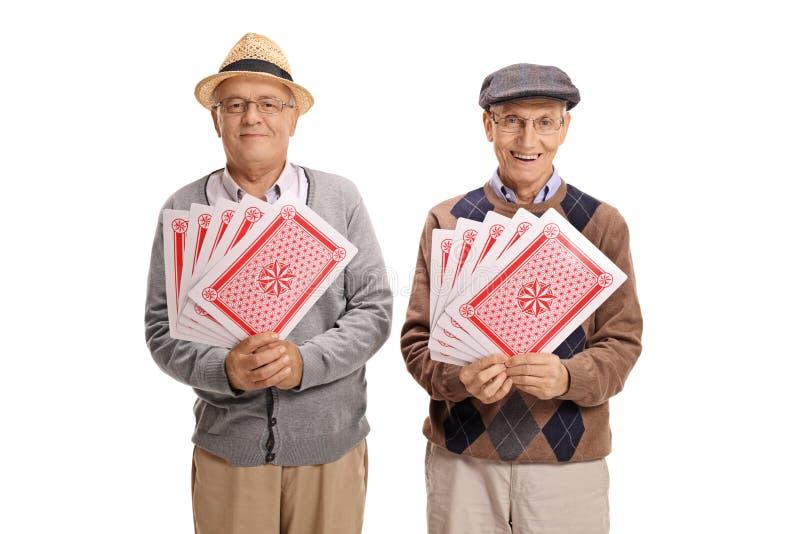 Twee bejaarden die met speelkaarten de camera bekijken royalty-vrije stock afbeelding