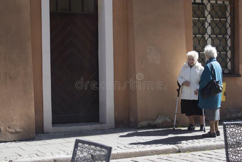 Twee bejaarden die op de straat spreken royalty-vrije stock fotografie