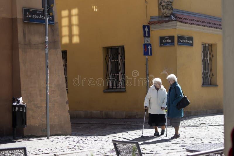 Twee bejaarden die op de straat spreken stock afbeeldingen