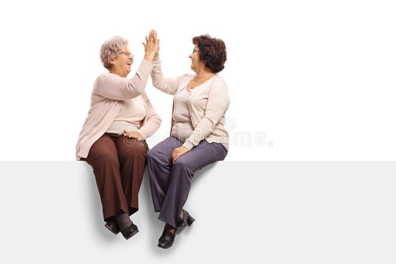 Twee bejaarden die op een paneel zitten en hoog-fiving elkaar royalty-vrije stock afbeelding