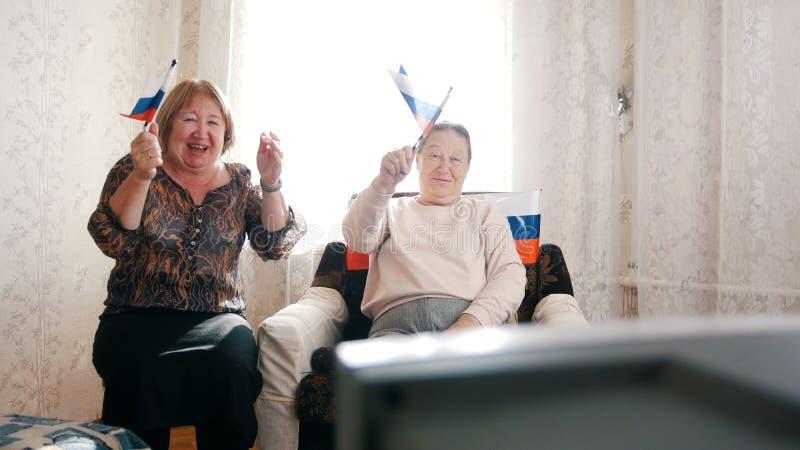 Twee bejaarden die op TV letten en Russische vlaggen golven royalty-vrije stock foto's