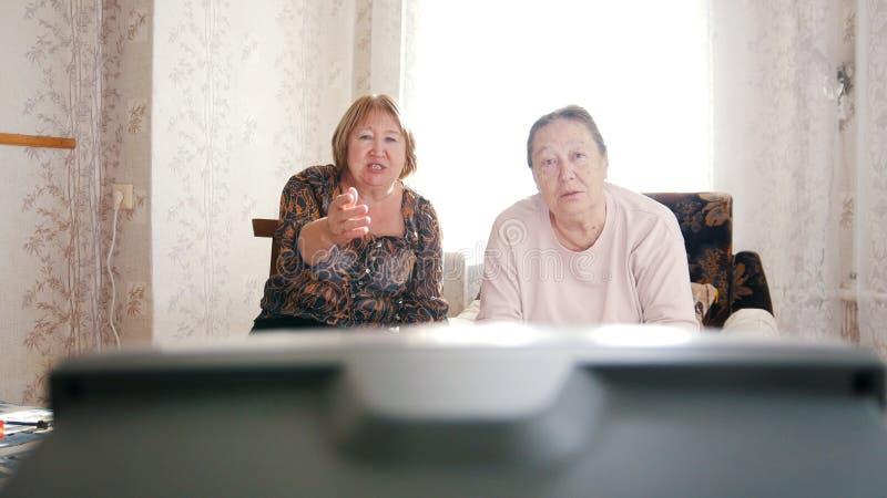 Twee bejaarden die op TV letten, die op het scherm richten stock afbeelding