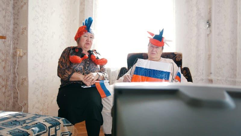 Twee bejaarden die op TV in Russische toebehoren letten stock foto's