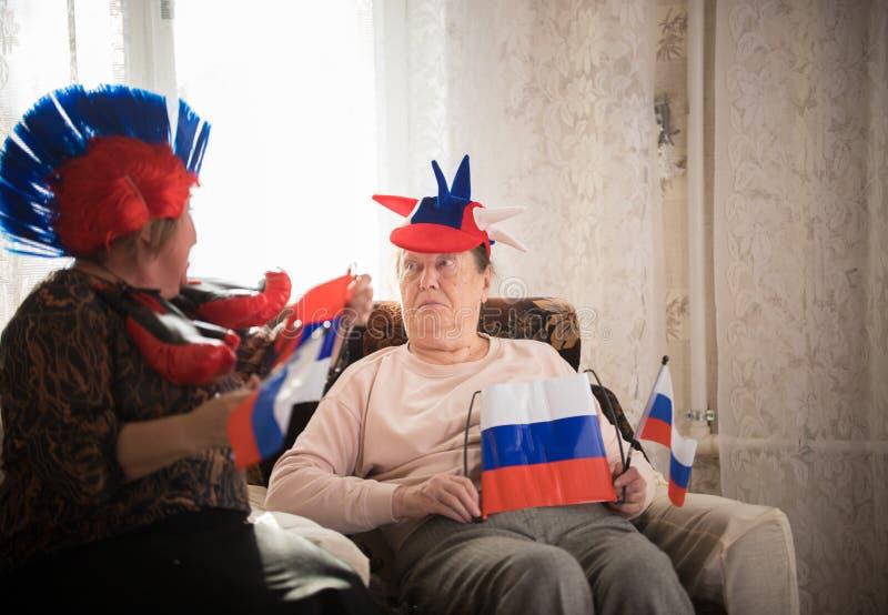 Twee bejaarden die in Russische toebehoren zitten die Russische vlaggen houden royalty-vrije stock afbeelding