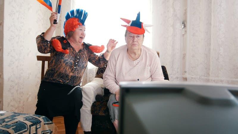 Twee bejaarden die in Russische toebehorentv letten op Één van hen die pret hebben royalty-vrije stock afbeelding