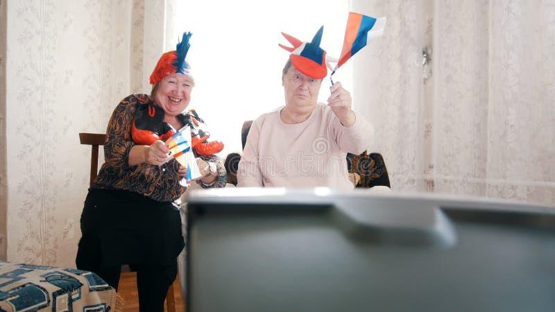 Twee bejaarden die in Russische toebehorentv letten op Het hebben van pret stock fotografie