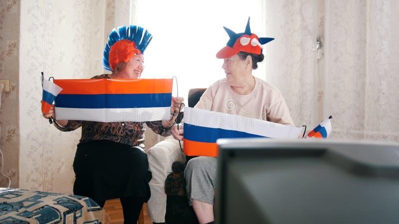 Twee bejaarden die in Russische toebehorentv letten op Russische vlaggen stock foto's