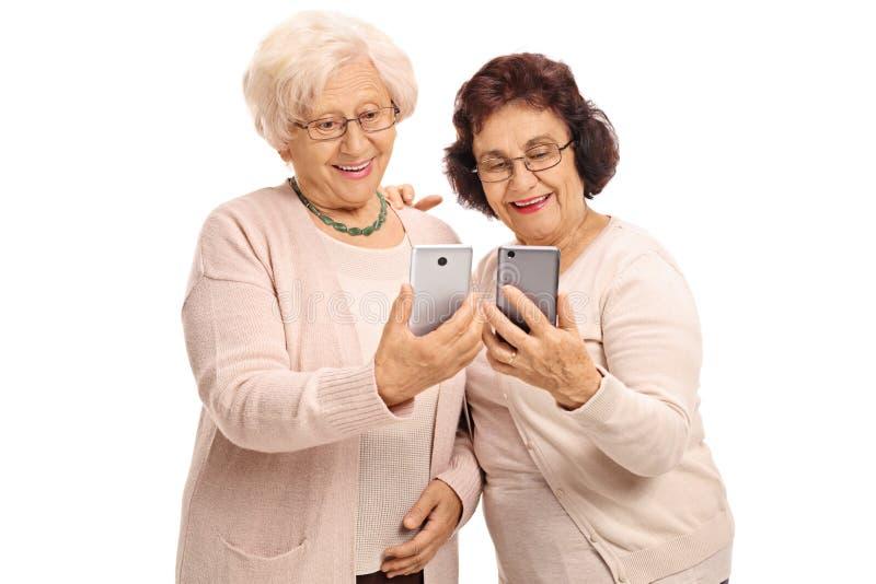 Twee bejaarden die telefoons bekijken stock afbeeldingen