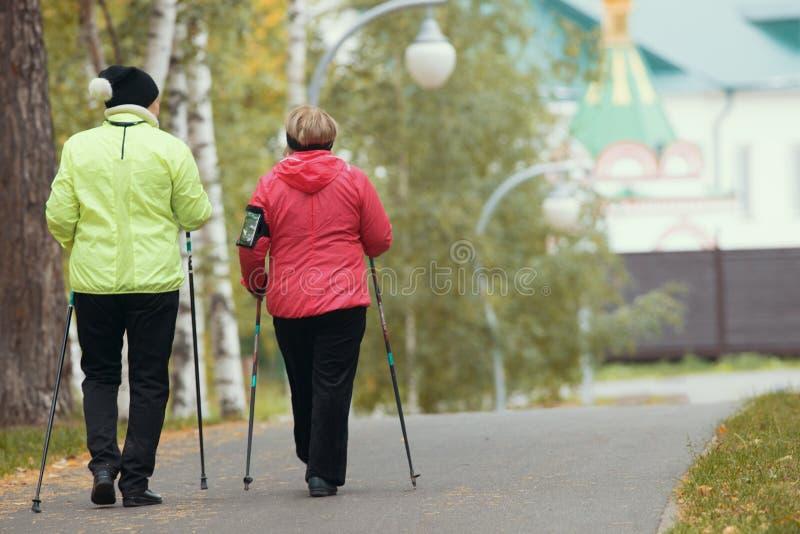 Twee bejaarden doen het Skandinavische lopen in het park De herfst Achterhoek royalty-vrije stock afbeeldingen