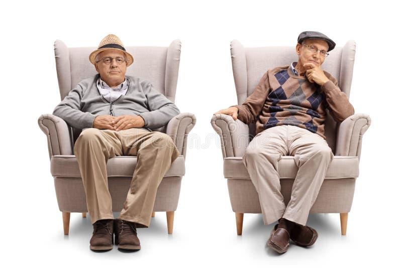 Twee bejaarden gezet in leunstoelen royalty-vrije stock afbeeldingen