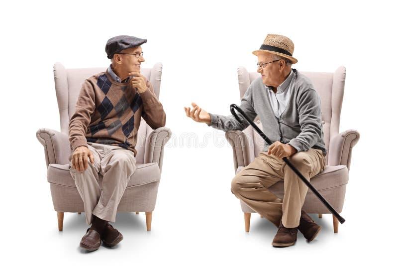 Twee bejaarden gezet in leunstoelen het spreken stock afbeelding