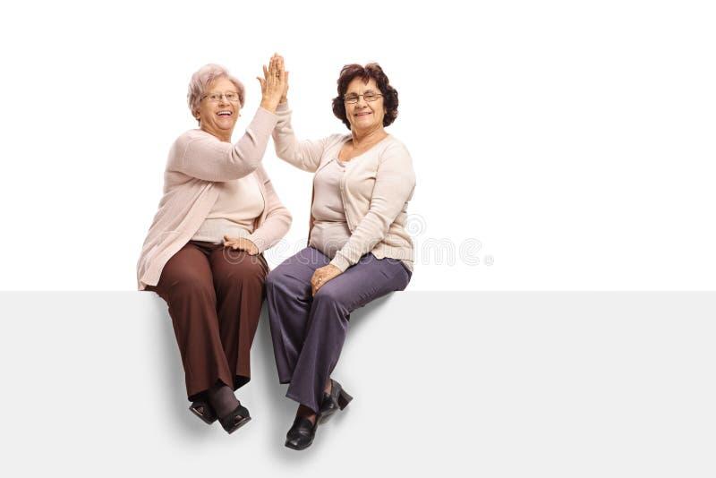 Twee bejaarden gezet op een paneel hoog-fiving elkaar royalty-vrije stock foto's