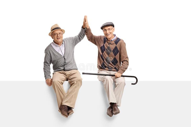 Twee bejaarden gezet op een paneel hoog-fiving elkaar royalty-vrije stock foto