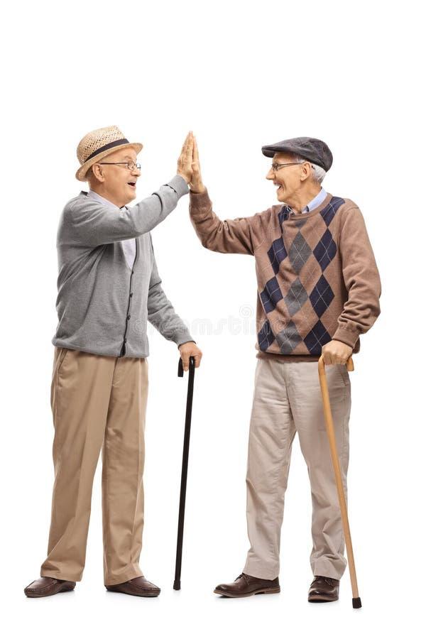 Twee bejaarden hoog-fiving elkaar stock foto's