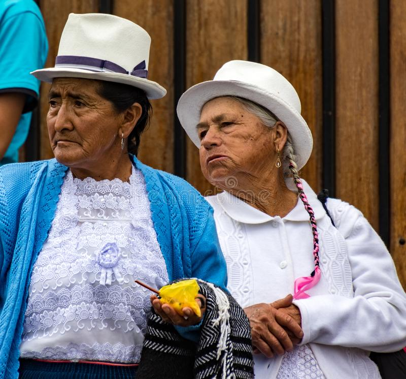 Twee bejaarden letten op het overgaan van parade met rente in Cuenca, royalty-vrije stock foto