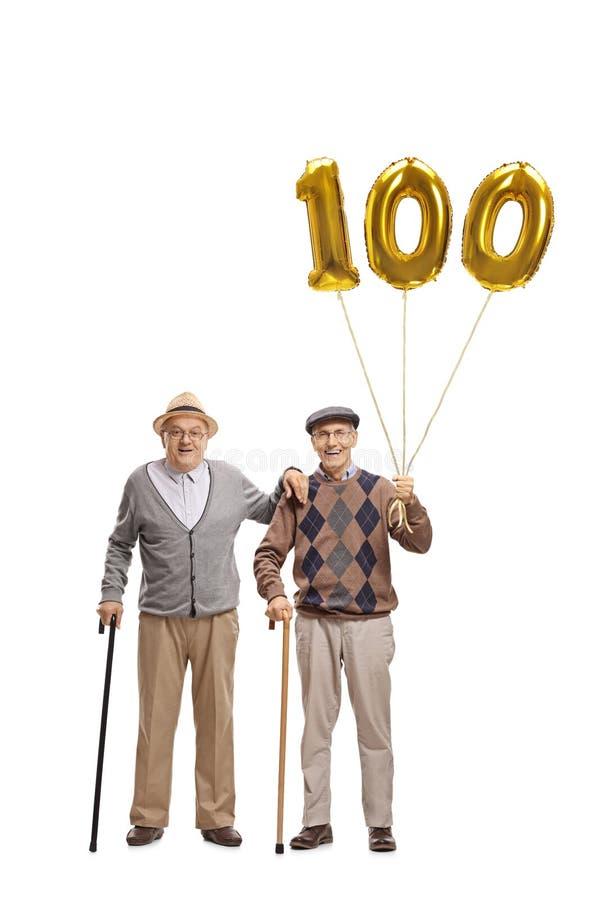 Twee bejaarden met een gouden aantal honderd ballon stock afbeelding