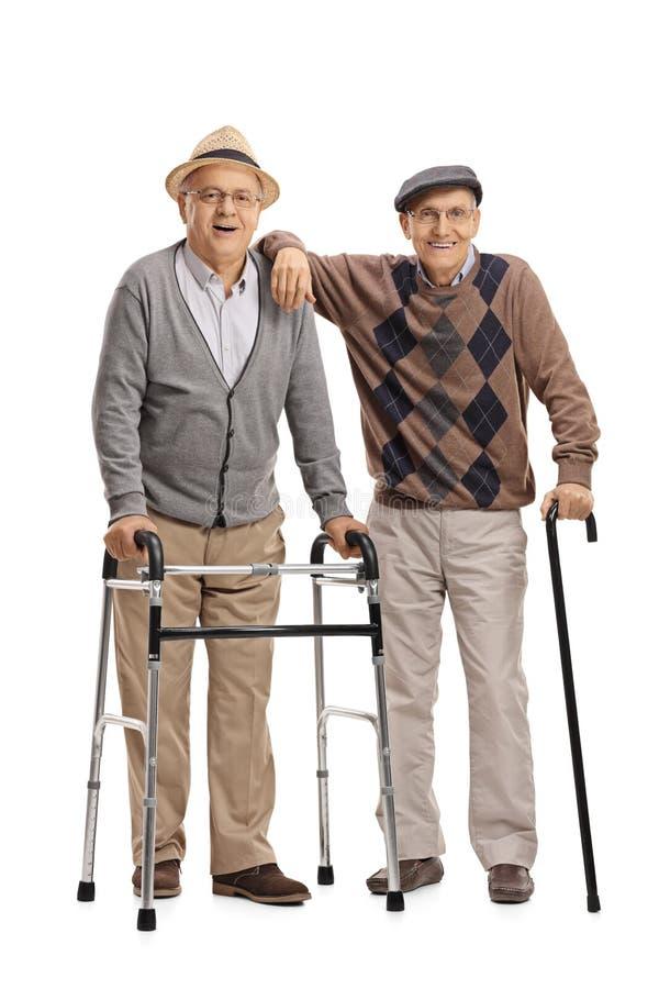 Twee bejaarden met een leurder en een riet stock foto
