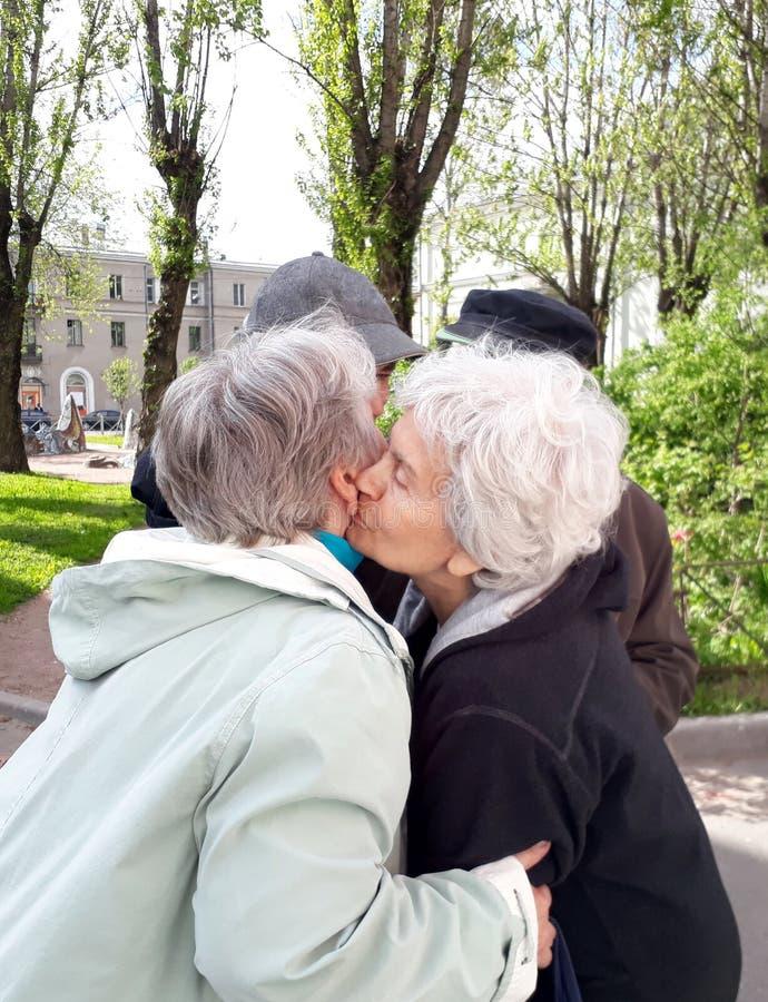 Twee bejaarden omhelzen & kussen bij scheiding royalty-vrije stock foto's