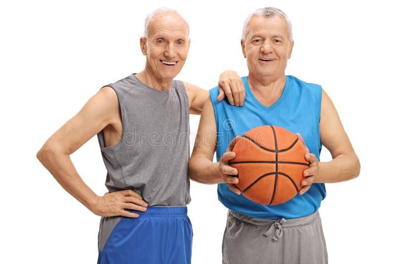 Twee bejaarden in sportkleding met een basketbal royalty-vrije stock afbeeldingen