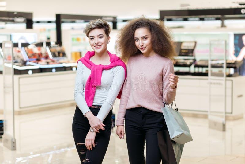 Twee beste meisjes die van de vriendencollega bij moderne winkelcomplexachtergrond stellen royalty-vrije stock foto's