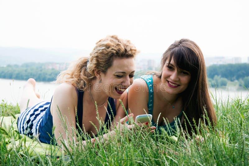 Twee beste meisjesvrienden die op het gras leggen royalty-vrije stock foto's