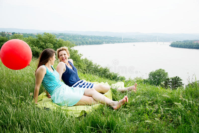 Twee beste meisjesvrienden die op het gras zitten stock foto's