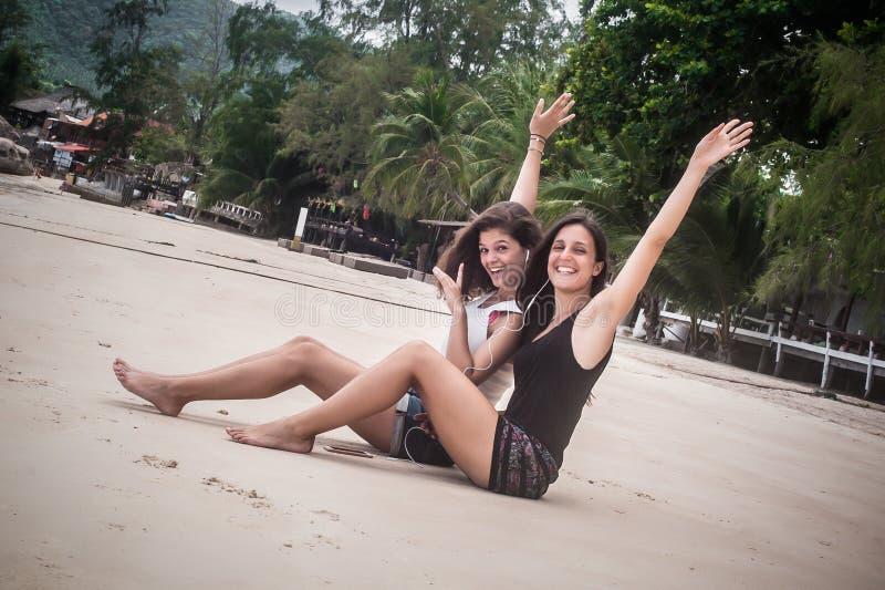 Twee beste vrienden het luisteren muziek op smartphone, die op strand genieten van royalty-vrije stock afbeelding