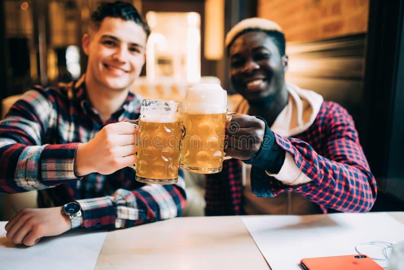 Twee beste vrienden of universiteitspartners die bier hebben bij bar Afro Amerikaanse mens die aan zijn Kaukasische vriend in bar stock foto