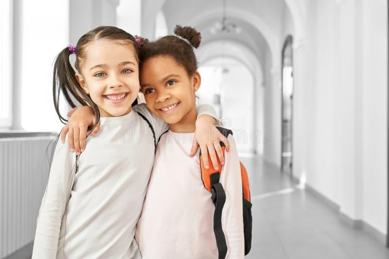 Twee beste vrienden weinig schoolmeisjes het omhelzen stock fotografie