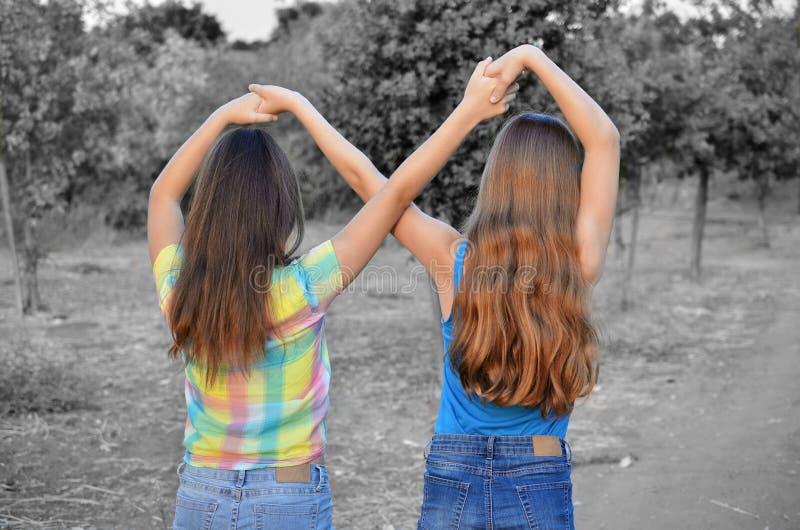 Twee beste vriendenmeisjes die een voor altijd teken maken stock afbeeldingen