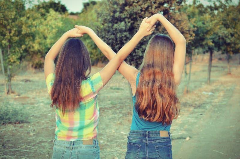 Twee beste vriendenmeisjes die een voor altijd teken maken royalty-vrije stock foto's
