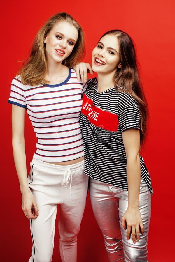 Twee beste vriendentieners die samen pret, stellen hebben emotioneel op rode achtergrond, besties het gelukkige glimlachen, leven royalty-vrije stock afbeeldingen
