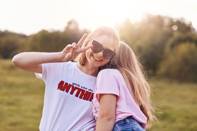 Twee beste vrouwelijke vrienden hebben openlucht, dwaze pret en omhelzen De vrolijke tiener met positieve glimlach, toont vredesg royalty-vrije stock afbeeldingen