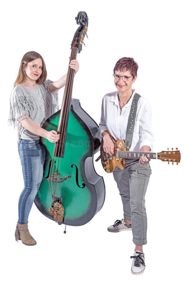 Twee bevindende vrouwen met dubbele baarzen en gitaar stock foto's