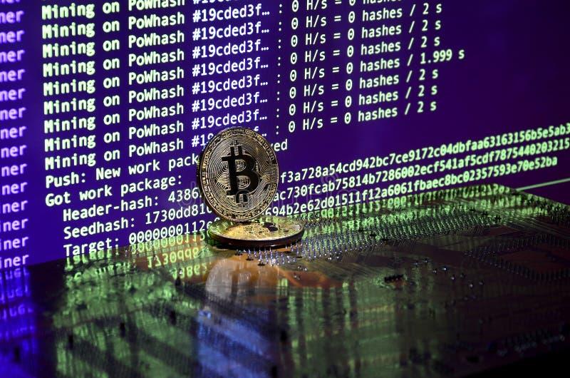 Twee bitcoins ligt op een videocardoppervlakte met achtergrond van het schermvertoning van cryptocurrencymijnbouw door GPUs te ge stock fotografie